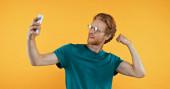 Rotschopf-Mann mit Brille zeigt Muskeln beim Selfie isoliert auf gelb