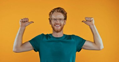 Smiling redhead man in eyeglasses pointing with thumbs at himself isolated on yellow stock vector