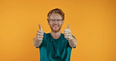 Cheerful  redhead man in eye glasses showing thumbs up isolated on yellow stock vector