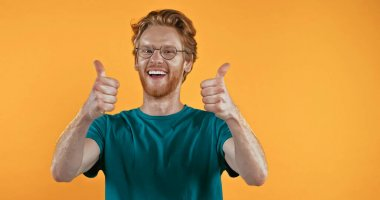 Cheerful redhead man in glasses showing thumbs up isolated on yellow stock vector
