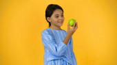 happy child holding green apple isolated on yellow