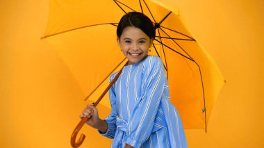 Cheerful child in blue dress standing under umbrella isolated on yellow stock vector