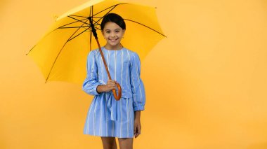 Happy preteen child in blue dress standing under umbrella on yellow stock vector