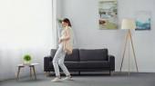 fröhliche, schwangere Frau berührt Bauch beim Tanzen im modernen Wohnzimmer