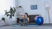 glückliche junge Frau in Sportbekleidung sitzt auf Fitnessmatte und macht Selfie zu Hause