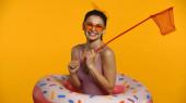 Fröhliche junge Frau in Badeanzug und aufblasbarem Ring, die eine Schaufel in Gelb hält