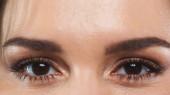částečný pohled na ženu s hnědýma očima hledící do kamery