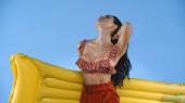 szexi nő fürdőruhában megható haj, miközben gazdaság felfújható matrac elszigetelt kék