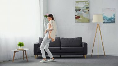cheerful, pregnant woman touching tummy while dancing in modern living room
