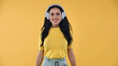Joyful woman listening music in wireless headphones isolated on yellow stock vector