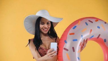 Cheerful woman in swimsuit and straw hat taking selfie with swim ring isolated on yellow stock vector