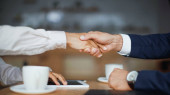 cropped view of businesswoman and businessman shaking hands in cafe
