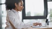 boční pohled na africkou americkou ženu psaní na klávesnici notebooku