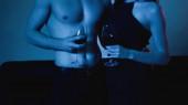 abgeschnittene Ansicht eines sexy Paares mit Weingläsern auf blauem Grund