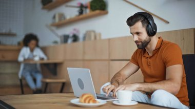 bearded man listening music in headphones while using laptop in cafe