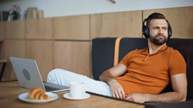 man listening music in headphones near breakfast and laptop in cafe