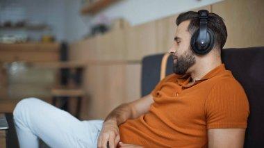 bearded man in wireless headphones chilling in cafe