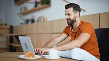 cheerful man listening music in earphones and using laptop in cafe