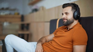 pleased man in wireless headphones listening music and chilling in cafe