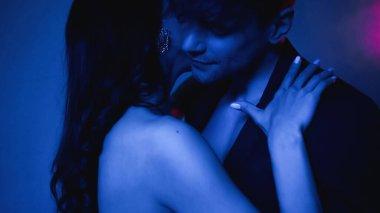 Woman embracing boyfriend in blazer on blue stock vector