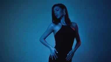 Elegant woman in black slip dress posing on blue background stock vector