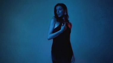 Brunette woman in black slip dress looking away on blue background stock vector