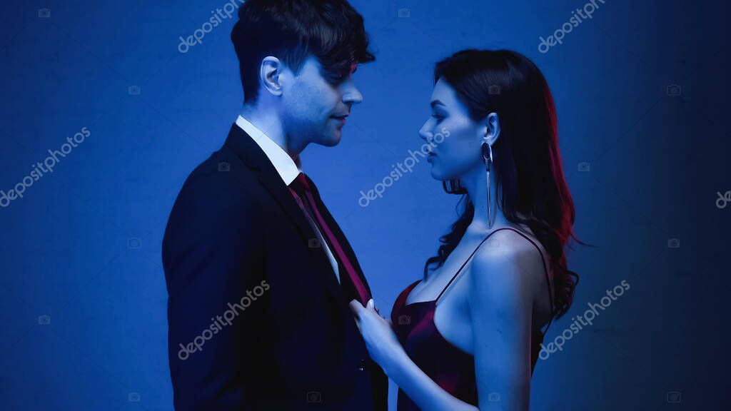 Side view of seductive woman pulling tie of man in blazer on blue stock vector