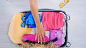 částečný pohled na ženu balící kufr s letním oblečením doma