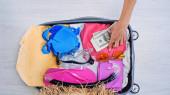 částečný pohled ženy, jak dává peníze na kufr s letním oblečením doma