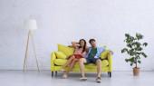 šťastný pár chlazení na žluté pohovce v obývacím pokoji