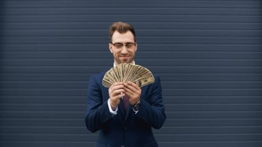 Cheerful businessman in suit smiling while holding dollars stock vector