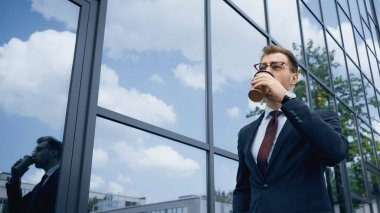 Businessman in glasses drinking coffee to go near building with glass facade stock vector