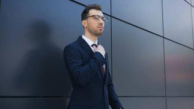 Businessman in glasses adjusting tie near building stock vector