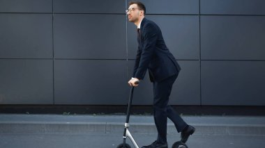 Full length of businessman in formal wear and glasses riding e-scooter near building stock vector