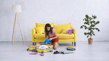 Brunette woman packing baggage near summer clothes on floor in living room stock vector