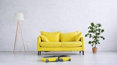 Yellow sofa near floor lamp, plant and suitcase on floor stock vector
