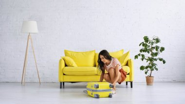 Brunette woman sitting and zipping yellow suitcase near sofa in living room stock vector