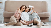 KYIV, UKRAJINA - 15. 4. 2019: Šťastná rodinka na smartphonu u joysticku na podlaze