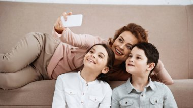Smiling mother taking selfie with kids at home stock vector
