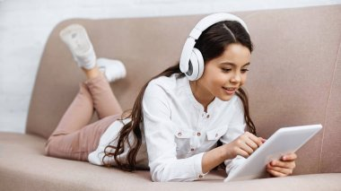 Preteen girl in headphones using digital tablet at home