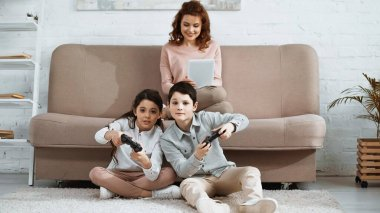 KYIV, UKRAINE -  APRIL 15, 2019: Kids playing video game near smiling mother with digital tablet on couch stock vector