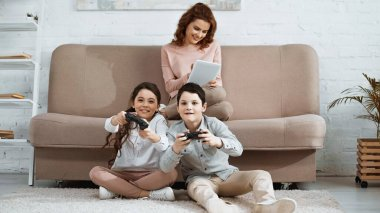 KYIV, UKRAINE -  APRIL 15, 2019: Positive kids with joysticks playing video game near smiling mother with digital tablet on blurred background stock vector