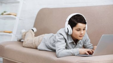 Preteen boy in headphones using laptop on couch