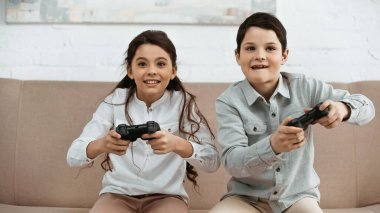 KYIV, UKRAINE -  APRIL 15, 2019: Positive kids playing video game in living room stock vector