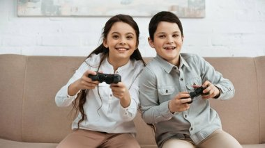 KYIV, UKRAINE -  APRIL 15, 2019: Smiling girl playing video game with brother in living room stock vector