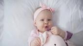 pohled shora na kojence držící měkkou hračku