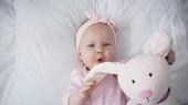 pohled shora kojenecké dívky držící měkkou hračku