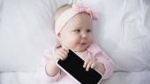felső nézet csecsemő baba gazdaság okostelefon üres képernyőn, és elnézett