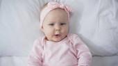 pohled shora kojenecké dívky v čelence při pohledu na kameru při ležení v posteli