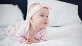 kojenecká holčička ležící na posteli při pohledu pryč